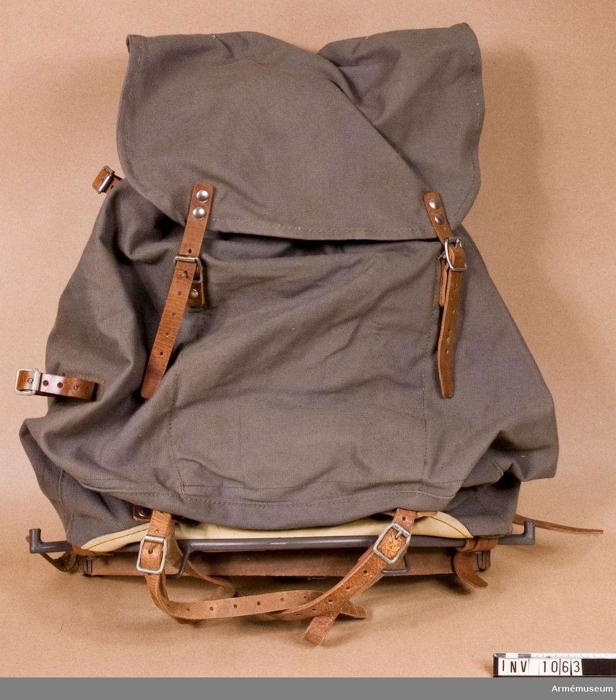 Samhörande nr är 1017-1059, 1062-1063, 1072-1073, 8216, 8216.Ryggsäck m/1939, m mes och bäranordning.Använd för utrustning 1939. Gjord av grå smärting. Upptill hopdragbar med ett snöre som är draget genom 18 öljetterade hål. Säcken har ett utanpåliggande lock med lädertampar som knäpps mot spännen på ryggsäcken. Det finns en läderskoning i säckens övre, bakre del för angörande av mesen. Läderhängslen dras i genom denna skoning och låser därvid mesen som låses även i sin nedre del på lika vis. Mesen är försedd med en kraftig rem som vilar i midjan på bäraren. Från remmen utgår en smalare rem som knäpps runt livet Reglerbar. Hängslena är försedda med hakar för fästande av annan utrustning. Under mesen, på ryggen, är säcken förstärkt med läder för att skydda mot skavning. Inuti försedd med en extra, öppen ficka. Har tillhört mobiliseringsutrustning vid Armémuseum.