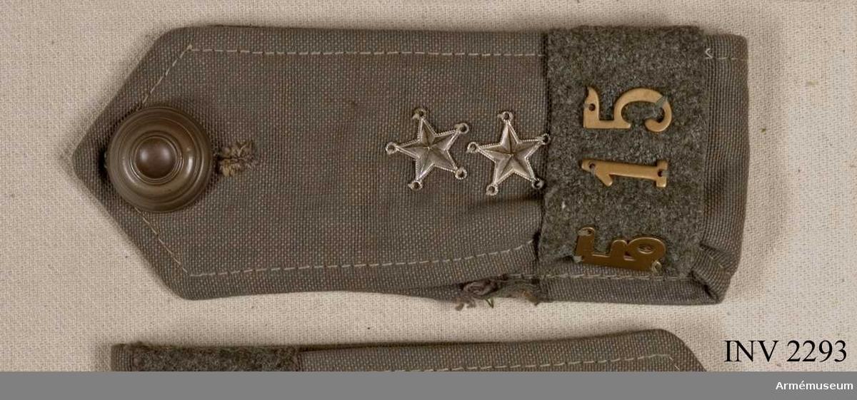 """Av grått, impregnerat vindtyg. Klaffen dubbelvikt och knäppt  med knapp m/1939.  Modellen av Kronobergs regementes m/1779. Två  silverstjärnor = löjtnants grad. Runt nederdelen är fäst en   hylsa av kommisskläde m/1939 med beteckningen """"Fo 15"""". Användes  på trenchcoat och vindjacka.Enl Wilhelm Wahrenbergs """"Försvarets knappar"""" har knappens utseende diskuterats i många år. Bl a är anfört att knappens motiv skall vara en läderkanon sedd framifrån."""