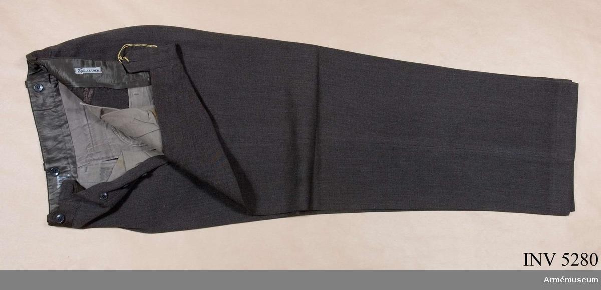 Storlek: 96. Mörkt gråbrungröna byxor, mörkare än vapenrocken, tillverkade i yllediagonal. Jylfknäppta med hällor i linningen. Sidfickor ooh en bakficka. Daglig dräkt.