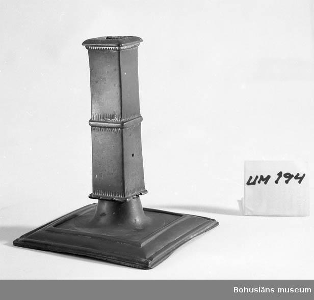 Ljusstake i malm eller möjligen mässing. Fot och ljushållare är fyrkantiga. Dekoren utgörs av reliefband och inpunsade trekantiga spetsar. Ljushållaren botten består av ett järnbleck.  Har inte putsats på många år därför har den en mörk patina. Enligt uppgift år 2012 från privatperson med goda kunskaper inom ämnet: Ljusstaken bör ha sitt ursprung i Frankrike, tillverkad någon gång från mitten av 1600-talet tills sekelskiftet 1700. Dekoren påträffas gärna i stakar från detta område. Även den fyrkantiga ljuspipan finns då och då på franska ljusstakar.  Ur handskrivna katalogen 1957-1958: Ljusstake, mässing Fyrsidig botten: 11,1 x 11,1. H: c:a 14. Obetydligt skadad.