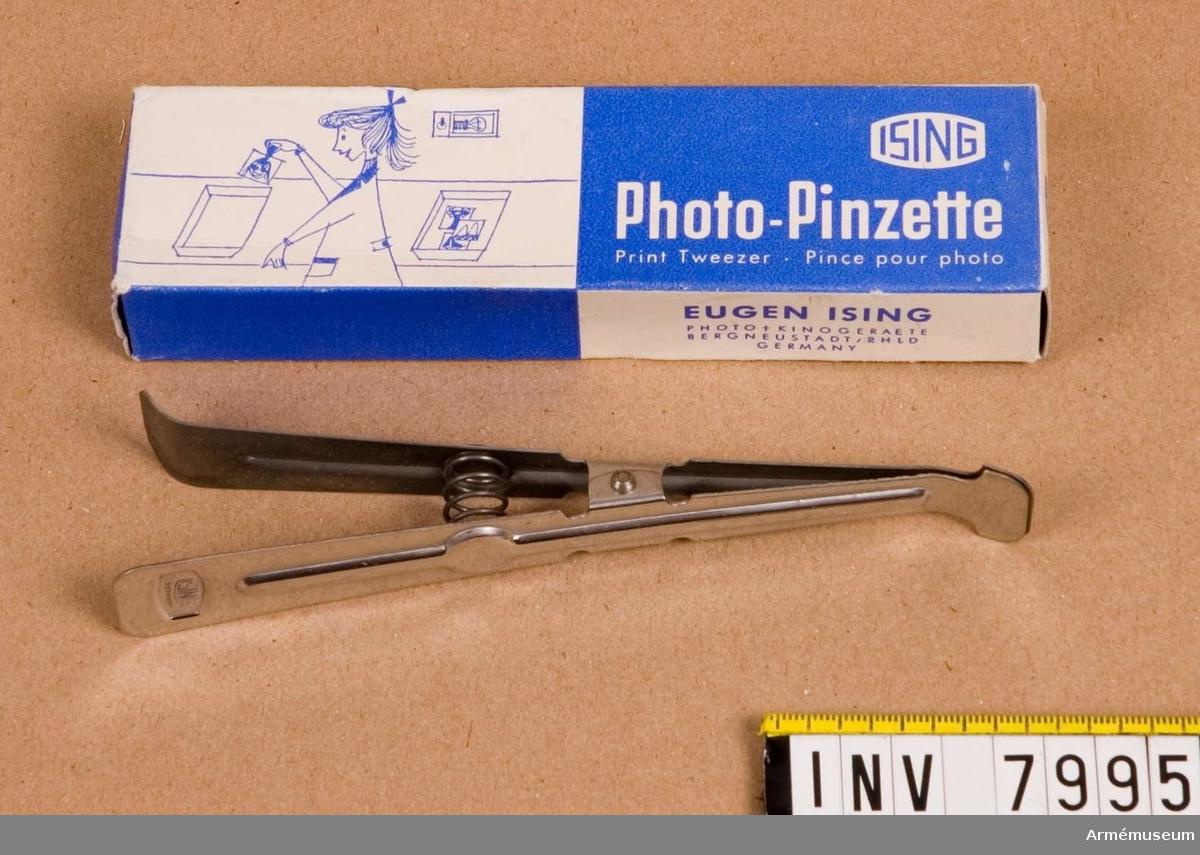 """Laboratorieklämma f fotografiskt bruk.Tillverkad av rostfritt eller syrafast stål. Märkt """"ISING"""" inom  en fyrkant och """"GERMANY"""".Blå/vit förpackning märkt """"Photo-Pincette Print Tweezer Pince pour photo"""" och """"EUGEN ISING PHOTO + KINOGERAETE BERGNEUSTADT/RHLD GERMANY"""".Ingår i fotomaterielsats 7 låda 1."""