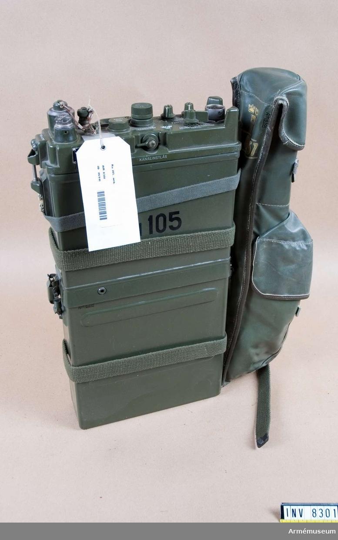 Tillverkningsnummer 3860 M 3955-105011.  Bestånde av 9 delar: Stationen ej helt komplett. Bärmes saknas. Radiostationen omfattar en stationsenhet med bärmes och två  packremmar av väv, en marschantenn, en normalantenn, en fjädrande antenndel, en antennströmsindiktor och en handmikrotelefon samt packficka av plastväv för dessa tillbehör. Märkt med tre kronor, Ra 105.