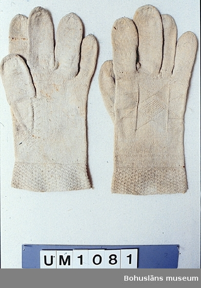 Handstickade fingervantar av tunt vitt (gulnat) bomullsgarn. Slätstickade, men med mönster av aviga och räta maskor nertill, vid tumkilen och i en stor stjärna på utsidan av varje vante. I Röhsska museets samlingar finns flera liknande vantar som tillhört högtidsdräkten i Bohuslän. Ett av de paren har tillhört en brudgum. Därför har även denna vante troligen tillhört en man. Stor, svagt synlig, fläck på vänster vantes ovansida. Rostfläckar. på insidorna. Mörknade.  Ur handskrivna katalogen 1957-1958: Fingervantar, ett par L. a) 26, b) 25 cm; vita, stickade av lingarn, m. mönster. Lane Ryr. Hela.  Lappkatalog: 78