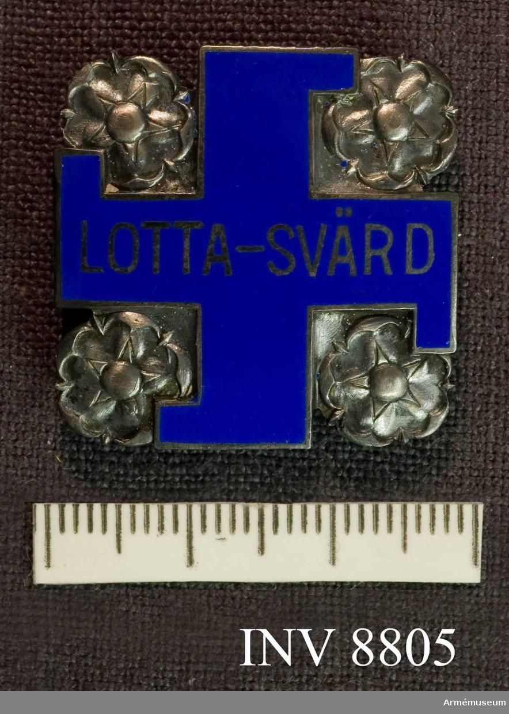 Ett märke i silver med Finlands rosor i hörnen och i  blå emalj ett svastikakors (hakkors) med texten LOTTA-SVÄRD. i silver. På frånsidan silverstämplar  och numret 15282. Broschen har suttit på Lotta-Svärd-dräkt AM 3650 som är en dräkt för medlemmar av Lotta Svärdföreningen i Finland.