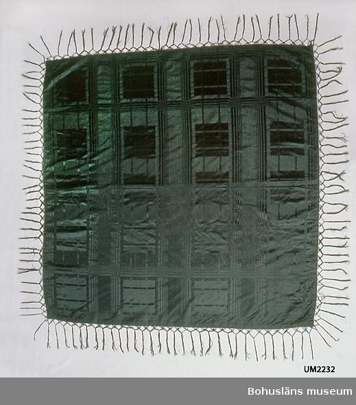 """571 Användningstid 1840-1890? 471 Tillverkningstid 1840-1890? 503 Kön KVINNA  Enfärgat svart kvadratisk schal av siden. Mot en botten i moaré finns ett rutmönster med 19 cm stora rutor i satin inuti ett rutverk bestående av smala satinränder i varp och inslagsriktning. Dessutom ripsränder som går genom de stora rutorna. Fållad med ett ylleband på baksidan. Påknutna fransar, ca 18 cm långa, lagda tre och tre över respektive under varandra och sammanknutna med ytterligare en knutrad till en tjockare frans Påsydd tygetikett med texten: """"Tillhört Fru Anna Malmgren född Kruse"""". Dateringen gjord med utgångspunkt från att moaré var modernt samtidigt som krinolinen ca 1840-1860 men även under 1880-talet. I gott skick, ett fåtal mycket små hål.  Ur handskrivna katalogen 1957-1958: Silkeduk, svart. Kvadratisk, c:a 1,60 x 1,60 m. (frans ej medräkn.)  Relativt välbevarad. Enl. påsydd lapp: Tillhört fru Anna Malmgren f. Kruse."""