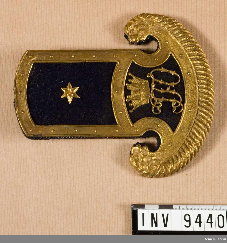 Epålett, underlöjtnant, kronprins Josef Frans Oscar. Utförd i förgyllt bronsarbete med blå klädesmattor. På nedre delen av epåletten monogrammet FJO och en furstlig krona. Epåletten har en orginell form så så till vida att den längst ner är halvmånformad och har i vardera sida ett lejonhuvud. Källa: Rulla 1845.