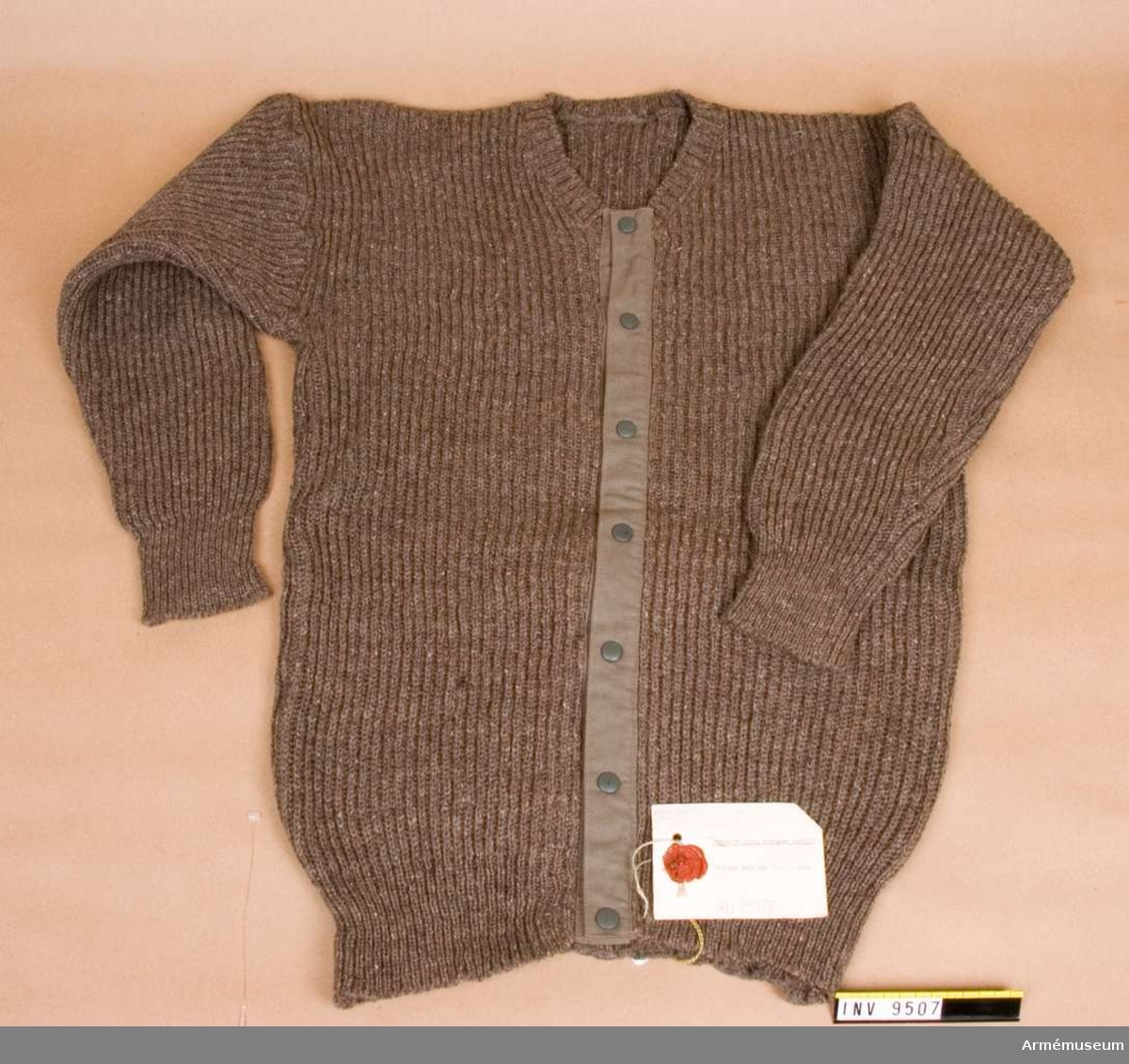 Stickad tröja med bomullstygslå mitt fram med tryckknappar. Maskinstickad avig och rät.