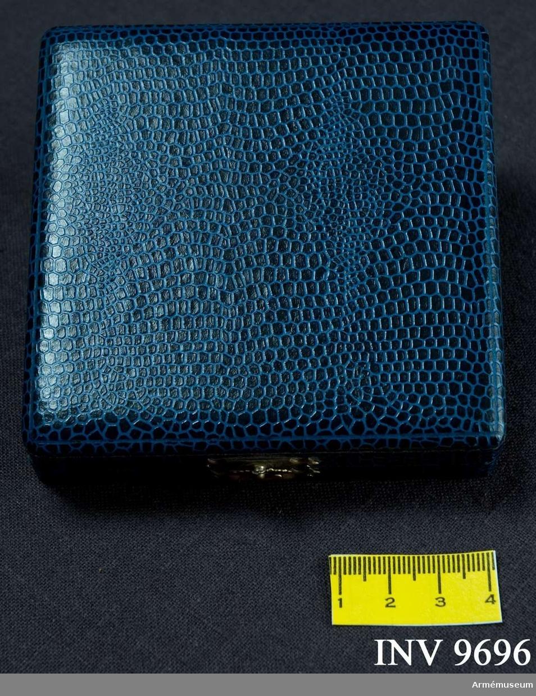 Samhörande nr är 9695-9696. Tillverkad av blå krokodilimiterad klot. Invändigt klädd i botten med blå sammet med urtag för medaljen. Locket är klätt med vitt sidentyg. Asken knäpps med ett litet spänne i gulmetall. Medaljen förvaras i asken.
