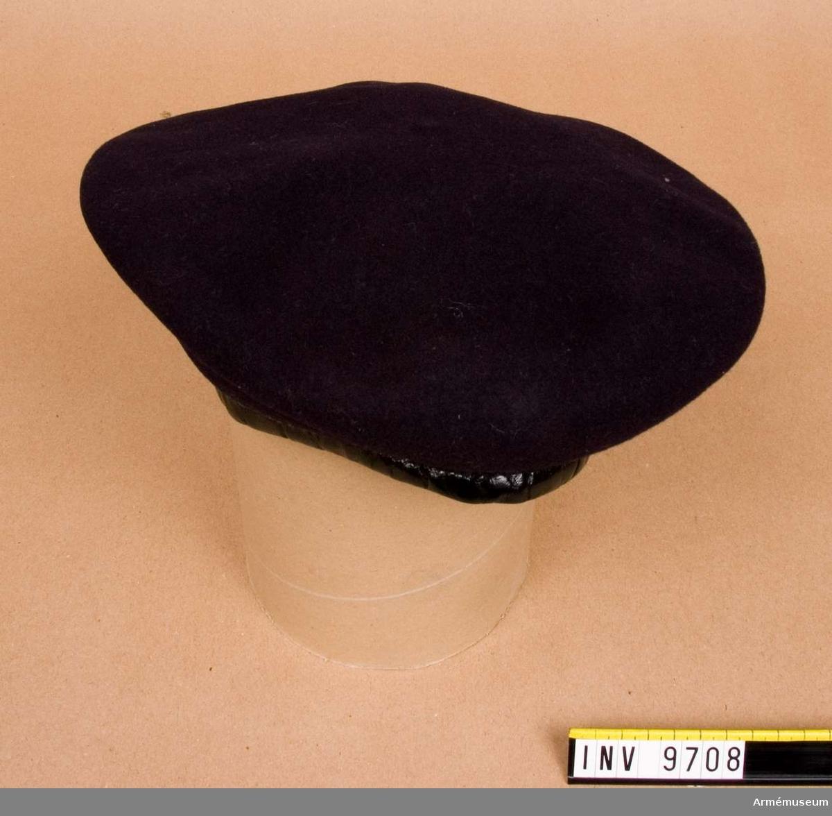 """Av mörkblått kläde med lackerad, svart kant av läder och rosett av svart sidenband. Vid sidan två lufthål. Märkt i fodret """"Ets Z.Beighaus. Oloron-Ste Marie, France. Storlek 56""""."""