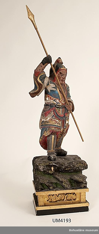 """Ur handskrivna katalogen 1957-1958: Japansk statyett Statyetten a) H. (utan sockel) 47,5 cm; Krigare i rustning; figurrik polykrom bemålning och förgyllning. Spjutet b) L. 64 cm; förgyllt. Sockeln c: I-III; mått, delarna sammansatta: H. 21, L. 22,5 Br. 16 cm; en i trä skuren """"klippa"""" på en underdel m. reliefarbetade speglar på sidorna. """"Klippan"""" målad imiterande naturen, underdelen förgylld och mörkbrun. Samtl. delar ngt skadade.  Lappkatalog: 10"""