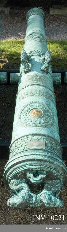 """Grupp A I.  Krigsbyte från den invid Dünamünde belägna skansen Neumünde, som den 11 dec 1701 erövrades av svenskarna. Följande inskrift syftar härpå: MED GUDS HIELP AF K CARL XII TAGIT MEDH  FESTNINGEN NEUMUNDE 11 DECEMB 1701.  Kanonen utmärker sig f.ö. genom sin högst praktfulla utstyrsel och fullkomlighet, vad tillverkningen beträffar.  På långa fältet: bilden av Solens gud.  På kammarstycket: kurfursten Johan Georgs förgyllda bröstbild och följande inskrift: JOHANN GEORG III / HERZOG ZU SAXEN / JCB CHURFURST 1686 och """"No 4"""".  På kammarbandet: WOLF CASPAR V CLENGEL ZEVG V ART OBRISTER. GOSS MICH ANDREAS HEROLD IN DRESDEN . (Wolfgang Caspar von  Clengel, tygmästare vid artilleriet överste. Andreas Herold i Dresden göt mig). Kammarsiraterna märkta """"N:6"""". Höger tapp """"IIIVX - IIIX"""". Mynningsplanet märkt """"53""""."""