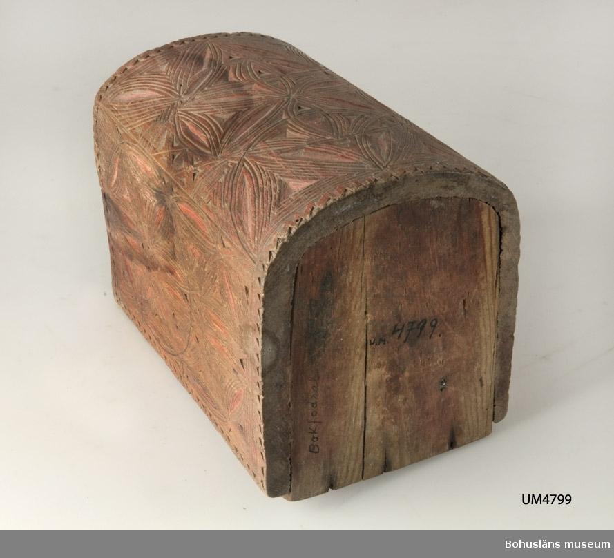 """Bokformat fodral med två skjutlock, varav det övre saknas. Utsidan har skurna rosetter i karvsnitt som går in i varandra. Runt kanterna löper en skuren sicksackrand. På en av """"kortsidorna"""" är ett horisontellt band på mitten med följande inskuret; """"1877 A.C.M.D"""". Målad med röd färg. Skjutlocket undertill saknar dekor, men har """"Bokfodral"""" skrivet med blyerts. Troligen en friargåva.  Litteratur: Fredlund, Jane, Stora boken om livet förr, ICA-förlaget, Västerås, 1981, s. 170-177. Nylén, Anna-Maja, Hemslöjd, Håkan Ohlssons förlag, Lund, 1978, s. 368-371.  Ur handskrivna katalogen 1957-1958: Bokfodral rött """"1877 A.C.M.D."""" Bottenmått: 14 x 12 H. 18,5. Av trä med karvsnitt. Utan lock. Rött. Föremålet helt.  Lappkatalog: 68"""