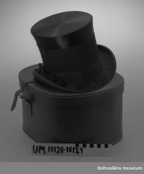 Hög hatt, försedd med sorgband. Inne kullen stämplad med guldbokstäver (slitna) Fredrik Friberg, Uddevalla. Inropad på Uddevalla Auktionskammare för 75:-.
