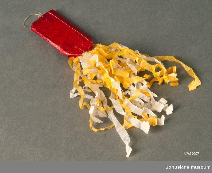Julgranskaramell i rött glanspapper med bokmärke på ena sidan, och krusad/veckad frans i gult och vitt silkespapper. Beige sytråd i glanspapperändan som upphängningsanordning. Prydnaden avsedd att hänga i julgran. Clara Nilsson (1866-1946) var mormor till givarna.