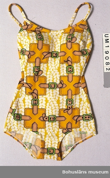 Föremålet visas i basutställningen Kustland,  Bohusläns museum, Uddevalla.  571 Användningstid 1970-TAL ? Hel baddräkt med smala axelband, djupt ringad i ryggen. Av mönsterstickad syntettrikå med en del glänsande trådar och tryckt mönster av rödgula (orange) kvadrater och ljusbruna bälten med gröna spännen mot en gul/vit spräcklig bakgrund. Invändiga styva kupor av glest tyg laminerat med genomskinlig plast.  Litt; Larsson, Marianne, Från badkostym till bikini ur Fataburen 1988, sid. 136-160.  Rowland-Warne, L, Fakta i närbild Kläder , Bonniers Juniorförlag AB Stockholm 1993, sid. 34-35. 990 Omkatalogiserat 1997-10-31 VBT