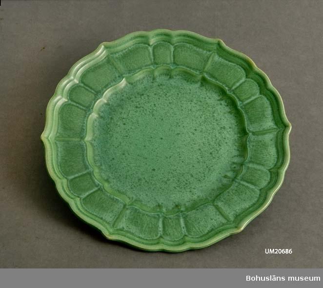Passformat bräm, modell W. Flammig grön glasyr.  Formgivare: Arthur Percy. Sammanhör med UM20685.