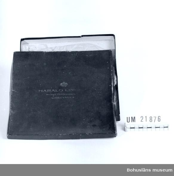 """594 Landskap BOHUSLÄN  Röd kartong, märkt med guldfärg: """"Harald Linder Kungl. Hovjuvelerare Uddevalla"""".  Emballage till tallrik UM21877.   UMFF 60:4"""