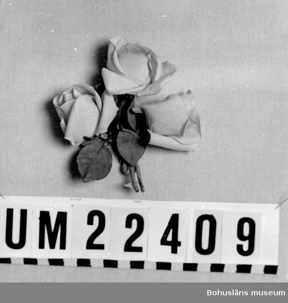 """594 Landskap BOHUSLÄN  Hattprydnaden består av tre ljusröda rosor med stjälkar och gröna blad. Har legat i en kartong med texten: """"100 Visitkort N:r 5 H.Råk"""".  UMFF 104:12"""