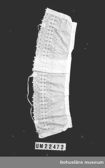 412 Förvärvstillst FUKTFLÄCKAR 594 Landskap BOHUSLÄN  Vitt linne med överdel samt axelband med engelskt broderi.  Knäppning ramtill med fyra tygklädda plåtknappar.  UMFF 108:8