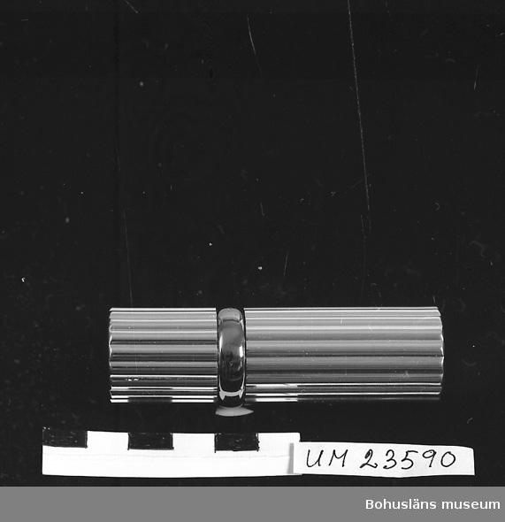 """594 Landskap BOHUSLÄN  Cylinderformad, godronnerad hylsa i vitmetall med gulmetallring mellan lock och behållare.    L. 7,7 cm.  Diam. 2,2 cm.                              På ena gaveln text i svart: """"Magie Lanco""""me, France"""".                     Förvaras i pappask, invändigt delvis klädd med vitt konstsiden.         Locket utvändigt klätt med grått sammetsliknande tyg. Längs bottenkanten guldpapper.                                        På undersidan påklistrad lapp med text: """"Magie, Atomiseur pow le sac.    Lanco""""me, Paris. Réf.6107 cont. 1/3 fl.oz"""".                            Askens mått: L.12 cm. B. 6.5 cm. H. 3,2 cm.                                Ur Langes varusortiment.     Langes Parfymeri låg i början av 1900-talet på Kilbäcksgatan, sedan vid Kungsgatan 9, i samma hus som Bokströms guldsmedsaffär. Butiken flyttade 1989 till Norra Drottninggatan 8.                                                      Affären Kungsgatan 9 fotodokumenterad och med intervju med innehavaren Marianne Karlsson, se Bohusläns museums bildarkiv, UMFA53250:0001 - 0024"""