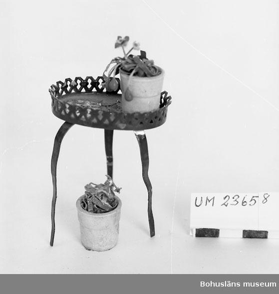 594 Landskap BOHUSLÄN  Oval skiva med uppstående genombruten kant. Tre ben. På skivan två fastsatta blomkrukor med blommor. Krukorna är av trä svarvade och vitmålade.  Neg nr. UM149: