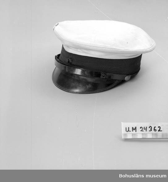 """106 OCM *743 594 Landskap BOHUSLÄN  Vit missfärgad kulle med svart kant runt om. Svart skärm och ett svart hakband vilket  ligger på skärmen. Hakbandet sitter fast med metallknappar med ett kors och en kungakrona på. Hör till skötarnas uniform """"S.J."""" skrivet inne i mössan.  Har burits av Sigge Johansson, född 1914. Han började på sjukhuset på 1930-talet"""