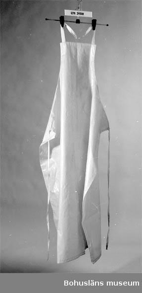 """594 Landskap BOHUSLÄN  Gul/beige. Bomullsband runt nacke och midja. Användes av personalen då de gav lavemang, sköljde """"kisselakan"""" och badade patienter."""