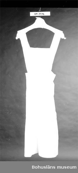 """594 Landskap BOHUSLÄN  Vitt. """"Kjol"""" med lapp för bröstet. Helt öppen baktill. En utanpåficka på kjolen.  På bröstlappen sitter två axelband, c:a 6 cm breda, vilka knäpps fast med vita  plastknappar, i kjolen bak på ryggen. På insidan vid nederkanten finns två stycken vita märklappar: 1) Ceris text: """"ST J"""" 2) Röd text: """"42"""""""