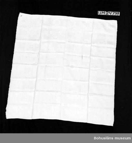 """594 Landskap BOHUSLÄN  Vit servett med damastmönster i satinbindning. Handvävd. Med utspridda runduddiga (blom-liknande) stjärnor i mittspegeln och bård avgränsad genom linjer, även den med samma stjärnor. I ena hörnet märkt """"EIH"""" i kedjestygn med vitt samt """"12"""" i korsstygn med rött. Handfållad. Insamlad av Berta Kleberg. UM6145 och UM18856 är servetter med samma mönster. UM6145 vävd i Uddevalla på 1840-talet. Troligen är även denna servett vävd i Uddevalla. Ytterligare uppgifter om gåvan UM024798 - UM024883,  se UM024798. Ett hål. Bristningar. Flera lagningar (stoppningar). Slitna kanter.  Litteratur: Becker, John m fl, Damask og drejl Daekketöjets historie i Danmark, Borgens forlag 1989, sid. 17-31 (vävtekniken). Damast på bordet, utställningskatalog från Nationalmuseum, 1990.  Topelius, Ann-Sofi. Damastduktyg och verksamheten vid Vadstena fabrik 1753-1843, Nordiska museets Handlingar 104. (bl a sociala förhållanden kring damast-tillverkning.)  Omkatalogiserat 1997-11-24 VBT"""