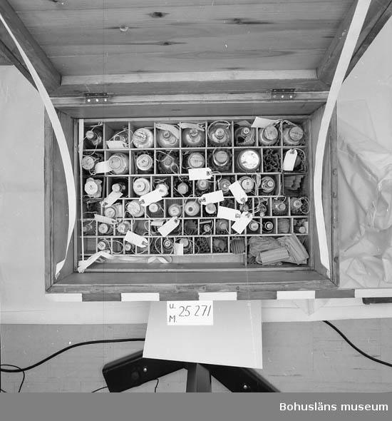 """471 Tillverkningstid 1899 CA 594 Landskap BOHUSLÄN  Bornö Hydrografiska station (Svenska hydrografisk-biologiska stationen på Stora Bornö) upprättades i privat regi 1902 för undersökningar av havsvattnet av kemist Otto Pettersson. Han var knuten till Holma säteri på fastlandet. Stationen leddes av oceanograf Hans Pettersson. 1932 övertogs stationen av statliga Fiskeristyrelsen. Fram till 1985 pågick verksamheten. Från forskningsstationen finns en unik mätserie vattenprover tagna varje dag på olika nivåer ned till 34 meters djup för analys av salthalt, temperatur, strömriktningar m.m.  Vid stationen fanns två forskningsfartyg. Detta skeppsapotek tillhörde troligen stationens första fartyg Skagerrak (år 1904). Skeppsapoteket är ej komplett. Lådan har två insatser som går att lyfta ur. Bärhandtag i metall på kortsidorna. Lås på framsidan. Nyckel saknas. I locket har det suttit en innehållsförteckning. Den har varit fastsatt med metallnitar i form av blommor. Innehållsförteckningen och nitarna ligger nu löst. Efter att lådan kommit till Bohusläns museum, har locket fått bomullsband som sitter fast i lådan som förstärkning. Kistan är lite vattenskadad.  Innehåll i översta insatsen: 1.Två njurformade fat i emaljerad plåt (vit med blå kanter).  2.En krokav järn.  3. Sju stycken cylindriska burkar i metall.  4. Grön ask av papper som saknar lock.  5. Ask av plåt med tysk text:""""Beiersdorf""""s Guttapercha-Pflastermull."""". Öppning på sidan. Lock saknas. (rostig). 6. Sex glasrör i varierande längder.  7. Ask av trä med lock. På locket är det handskriven text: """"Atropin - morfin - opiumgelat. Ögondroppar, penslar, små halspenslar Febertermomenter. Fingertutor, musekplåster Säkerhetsnålar, Klorpjott kalipastiller Kork, 2 sprutor, morfinspruta, etiketter tomt nedre afdelen."""" I asken ligger en spatel av trä samt en träskiva med fyra cirkelrunda hål.  8. Etiketter från Apoteket Enhörningen i Göteborg.  9. Ask med Lackmuspapper.  10. Ask med Koppar.tife. 11. En bunt med pappersfilter.  1"""