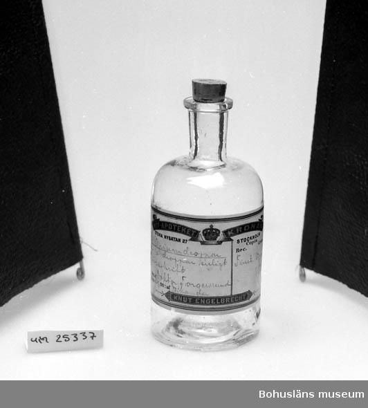 """594 Landskap BOHUSLÄN  Kork med siffran 52. Etikett med text: """"HOF-APOTEKET KRONAN STORA NYGATAN 27 STOCKHOLM Rec.Copia. Gram. Opiumdroppar 50 - 10 droppar enligt föreskrift Finet. Opium 150 Ord. af Doktor Torgersruud Exp. d. 3/8 1903 Nikander KNUt ENGELBRECHT"""". Innehållet är tömt av Bohusläns museum."""