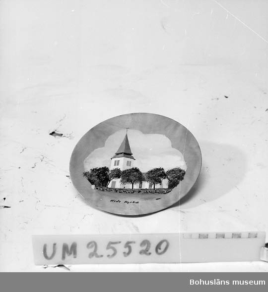 """Konkav tallrik med upphägningskrok.  Målning av Hede kyrkas exteriör och kyrkogård med mur och trädrad.  Målningen signerad """"OE."""" Underst svart text: """"Hede kyrka"""". Föremålet inköpt på Uddevalla Auktionskammare."""