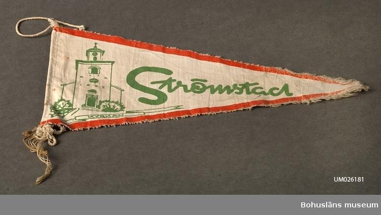 """Trekantig vimpel. Naturfärgad bomull med textiltryck. Röd kant och i grönt bild av Strömstads kyrka och namnet """"Strömstad"""". Sammanhör med UM026180 - UM026184. Användar- och förvärvsuppgifter se UM026180"""