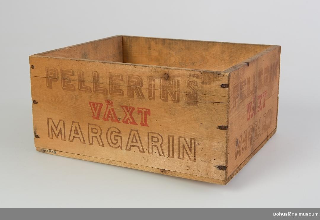 """Rektangulär furulåda hopspikad. Lock saknas. Har varit rakt påspikat. På samtliga fyra sidor påtryckt brun och röd text: """"Pellerins Växt Margarin"""". På bottnens undersida påtryckt text i brunt: """"Pellerins Margarin"""". Personuppgifter om ägaren se UM026259"""
