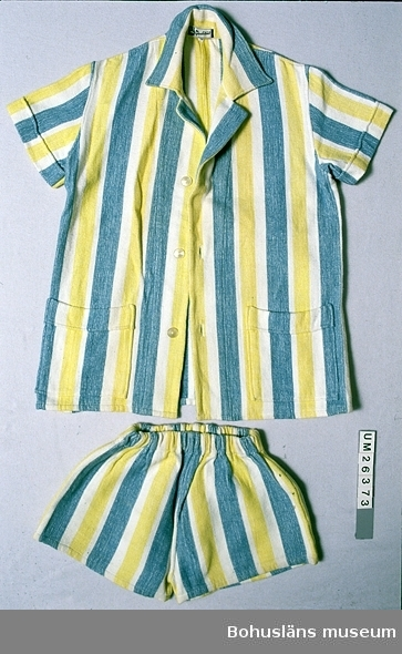 """410 Mått/Vikt JACKA: L 82 B 77 SHORTS: L 35 B 59 CM Stranddress bestående av shorts och jacka. Av varptrikå med """"inslagna"""" trådar även på tvären. (Tillverkad i raschelmaskin ?). Långrandig i vitt och bredare ränder av gult och blåtonat grönt. Shortsen har ca 5 cm korta ben, resårband i kanal i midjan. Jackan är av rak modell, har korta ärmar, krage med litet slag, fyrkantiga utanpåfickor nertill, knäpps fram med knappar och knapphål. Sydda veck vid fickornas överkant och ärmarnas nederkant ger en dekor som liknar slag. I både shorts och jacka finns fastsydda vit/svarta tygetiketter med texten """"AS Qualität"""" och bilden av ett spader. Troligen från tidigt 60-tal. """"Kraftiga"""" pastellfärger var populära då.  Personuppgifter om givaren se UM 26370."""