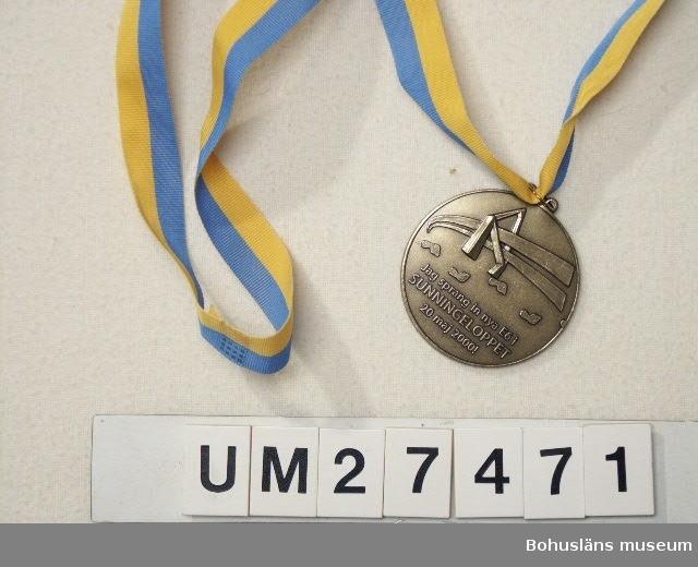 """Rund medalj av gulmetall med hänge med ripsband i gult och blått att hänga om halsen. På medaljens ramsida ingjutet i relief en logotype av Sunningebron samt därunder texten:   """"Jag sprang in nya E6 i SUNNINGELOPPET 20 maj 2000!"""". På baksidan ingjutet  """"E6 Sunningeleden"""" med Uddevalla bron samt sponsorernas namn och logotyper: """"UDDEVALLA KOMMUN, PEAB, Vägverket PRODUKTION, Vägverket, ODDEVOLD"""".  Medaljen har använts vid invigningen av Uddevallabron i Uddevalla kommun den 20 maj 2000 på det s k Sunningeloppet, en löptävling med 7300 deltagare i alla åldrar med Oddevold som arrangör. Man kunde välja mellan fyra olika distanser; en """"halvmara"""" om knappt 21 kilometer, ett """"millopp"""" på 10,7 kilmoeter, en fyrakilometers-bana och ett """"knattelopp"""" om två kilometer. Varje tävlande bar en T-shirt med nummerlapp och erhölll  efteråt  en medalj.  Litt: Sunningeleden. Den vackraste genvägen. Uddevallabron. Red. Viveka Overland, Uddevalla 2000, s. 136 - 145."""