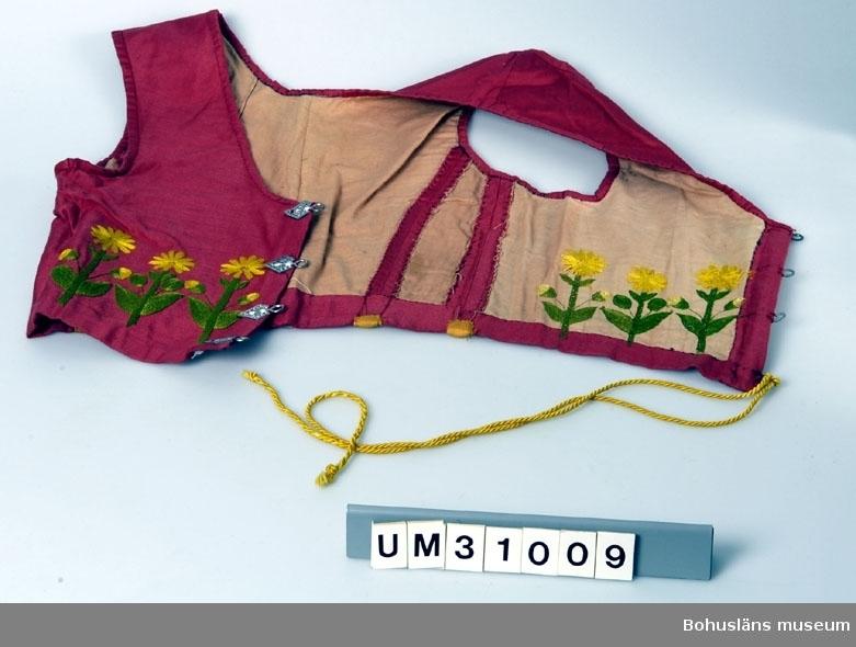 Livstycke av röd bomull, fodrat med rosafärgat bomullstyg. På framsidan tre broderade blommor på varje sida, sydda i stjälkstygn och schattérsöm med silkeliknande garn, troligen Moulinégarn = merceriserat bomullsgarn. Stjälkarna är gröna, blommorna klargula. Blommönstret är sytt genom både yttertyg och foder. Baktill är intagningarna dekorerade med fyra remsor av gult bomullstyg, vilka också täcker skenor, eventuellt av metall. Livstycket snörs fram med en gul silkessnodd genom åtta hyskor av tennliknande metall. Livstycket är inte alldeles välsytt. Hål i ryggdelens tyg vid förvärvet.