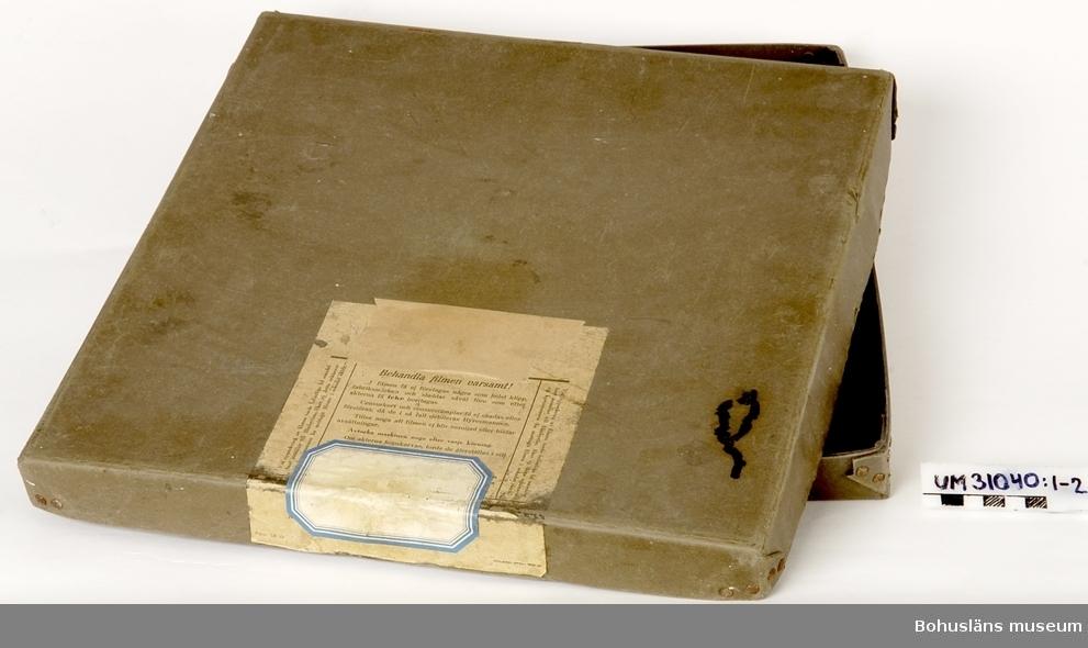 Tvådelad filmrullekartong (:1-2) av grå kraftig papp (lock och botten) innehållande stämplat, rosa granskningskvitto (UM31040:3) från Statens Biografbyrå för filmen Kastrullresan, daterad 1951, UM31035 och UM31038 spelad på projektor UM31031.  Projektorn är tillverkad av AEG på 1920-talet och har använts i Folkets Hus i Sjöbol vid Lysekil.  Till projektorn hör en lång rad delar och olika tillbehör, UM31031 - UM31062.  För ytterligare upplysningar om filmprojektorn, dess olika delar och användning, se UM31031.