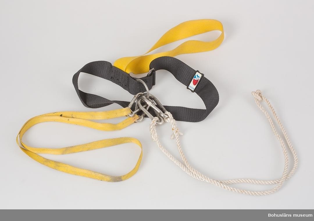 """Livsele av vävda band av polyester, gula och svarta.  Svart justerbart midjeband, på spännet med märkningen: """"OLIVECRONABÄLTET STECE"""" I det svarta bandet sitter ett gult band som sannolikt skall sitta runt ena benet samt en kraftig metallring. Tillkommer ett längre smalt gult band samt en tvåslagen livlina, båda med kraftiga karbinhakar i ändarna."""