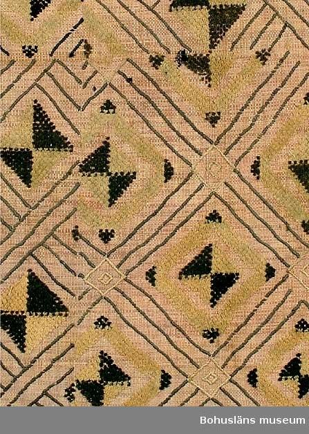 """Text till webbutställning """"Från när och fjärran"""" presenterad på Bohusläns museums hemsida åren 2009 - 2013: Vävnad av rafiabast med broderat mönster, delar av mönstren har flossakaraktär, 80 x 78 cm. Mönstren, som täcker hela den vävda tuskaftsbottnen, består dels av linjer, dels av ytor med sammets- eller flossakaraktär. Typisk är att mönsterformerna plötsligt ändrar karaktär och symmetrin saboteras på ett befriande sätt. Baksidan är nästan enfärgad, broderiet syns endast i svag relief.  Basten kommer från rafiapalmens långa blad, Rafhia farinifera. Bladen kan bli upp till 20 meter långa. I Sverige träffar vi på materialet under benämningen trädgårdsmästarbast.  Textilier av detta slag utfördes i Kasai-området i södra delen av Belgiska Kongo, nuvarande Demokratiska republiken Kongo. Där fanns från 1600-talet Kuba-riket med Shoowa-stammen, som var känd för sin mycket speciella och högt skattade broderiteknik. Det var männen som vävde, medan kvinnorna broderade de geometriska mönstren i dessa prestigetextilier, ibland använda som betalningsmedel. Gåva av Sjökaptenen och Riddaren Elmer Göransson år 1961.  Uppgifter om givaren: Under sin 30-åriga vistelse i Belgiska Kongo skötte Elmer Göransson (1872-1964) under många år transporter på landets floder. När han år 1932 avslutade sin tjänstgöring var han både skeppsfartygsinspektör för hela den belgiska flottan i övre Kongo, t. f. chef för hydrografiska tjänsten samt hamnkapten i Leopoldville. Han var samlare av bl.a. vapen, textilier och träkärl. I omgångar från 1919 skänkte Göransson afrikanska föremål till Uddevalla museum. Han kom att bli en av museiföreningens hedersledamöter. Vid sin bortgång 1964 var han bosatt i Kungsbacka.  Artikel i Bohusläningen från måndagen den 1 november 1937. """"Vittberesta bohusläningar berätta. Upplevelser under 30-årig vistelse i Belgiska Kongo. Kapten Elmer Göransson. Folk och sedvänjor under ekvatorns glödande sol."""" ______________________________________________________  Kontinent: Afrik"""