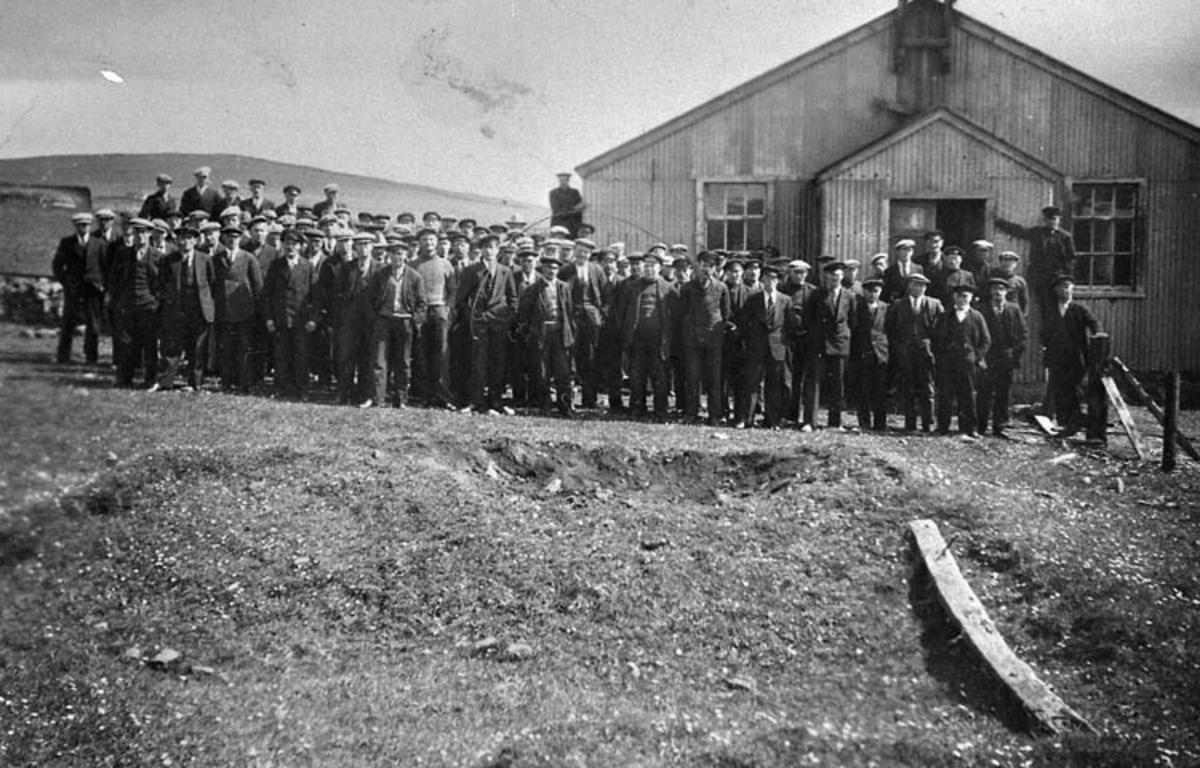 """Enligt tidigare noteringar: """"Bohuslänska fiskare utanför Svenska Kyrkan i Baltasound, Shetland, pingstdagen 1933.  Repro av foto tillhörande Ernst Gullman""""."""
