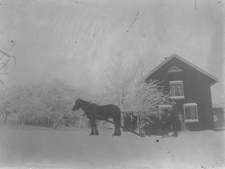 """Enl. text i blå bok: """"Häst och släde med personer framför hus."""""""