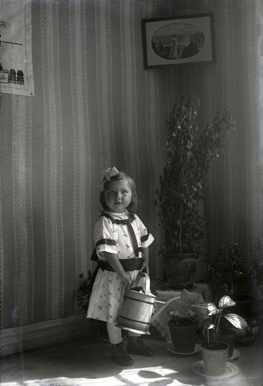 Flicka vattnar krukväxter