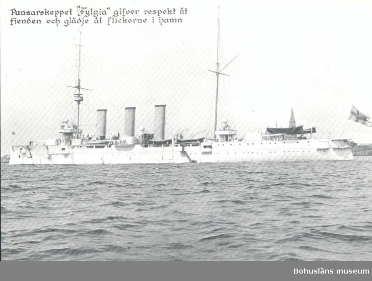 """Tryckt text på kortet: """"Pansarskeppet """" Fylgia"""" gifver respekt åt fienden och glädje åt flickorna i hamn."""" """"Carla Förlaget Lysekil. Tel. 0523/10919."""""""