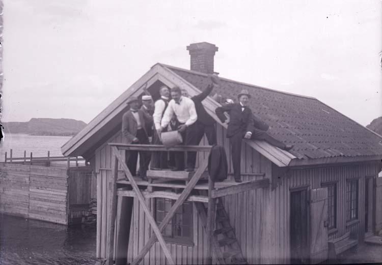 """Enligt text som medföljde bilden: """"Henån, Engelbert, Valter, Primus m.fl. vid pumpen på Badhuset. 28/7 1901."""""""