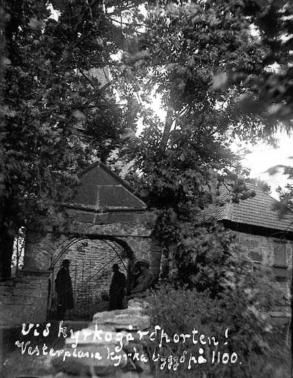 """Enligt text på fotot: """"Vid kyrkogårdsporten, Vesterplana kyrka byggd på 1100""""."""