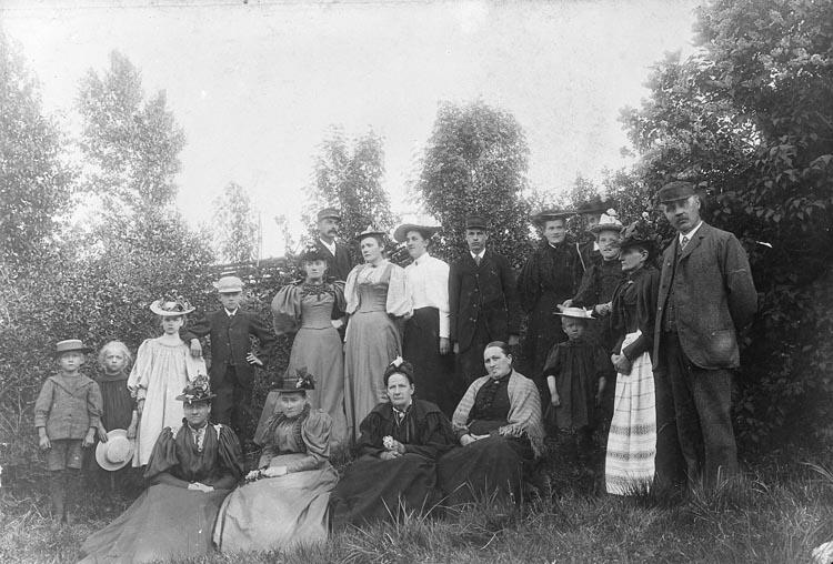 """Enligt fotografens noteringar: """"Minne från Färgelanda- Prästinnan Ferlin från Färgelanda -i mitten. ...? Gammal grupp från 1900-talet- medlemmar af Nordströms."""""""