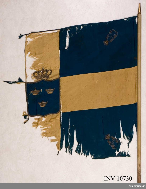 Grupp B.  Duken är blå med ett gult kors tillverkad av sidentaft. Kantband av blått sidenband. Blått mittfält med tre kronor kantad med   guldgalon under sluten krona, broderad i guld med rött foder. I hörnen Carl XIV:s namnchiffer. Stång av vitmålad furu. Doppsko av mässing. Spets saknas. Holk. Kravatt av blått och gult fansiden med tofs 130 mm av silke, gult och guldbuljon. Kravatten saknas i berget. Längd 1020 mm, bredd 200 mm. Fodral av svart kläde med spets och dragsko. Ficka av läder.   Längd 1840 mm, bredd 180 mm.