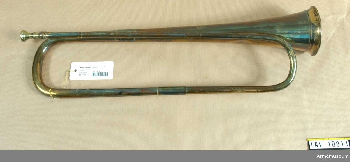 """Grupp B III.  Signalhorn i F, av mässing i en vindling.  Signerad på klockstycket Ahlberg & Ohlsson (upprättstående stil). Klockstycket vidgas föga.  """"Jägarehorn"""" förut använt av hornblåsare vid I 1.  Från Svea Livgardes musikkår enligt K.A.I.D skrivelse 19010117. / A . Lillehöök 1939."""