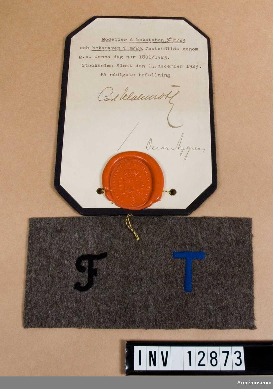 Grupp C I. Modell på bokstaven F och bokstaven T m/1923, fastställda genom go den 14 december nr 1801 år 1923. Deposition från Arméförvaltningens intendenturdepartement, modellkammaren.  För axelklaffar.